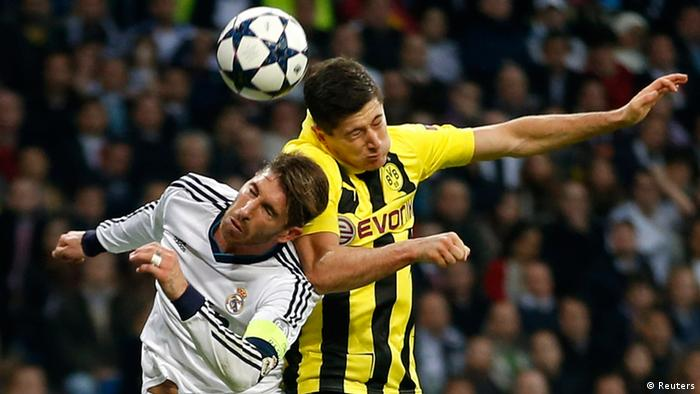 Real Madrid's Sergio Ramos and Borussia Dortmund's Robert Lewandowski (R) jump to head the ball during their Champions League semi-final second leg soccer match at Santiago Bernabeu stadium in Madrid April 30, 2013. REUTERS/Sergio Perez (SPAIN - Tags: SPORT SOCCER TPX IMAGES OF THE DAY)