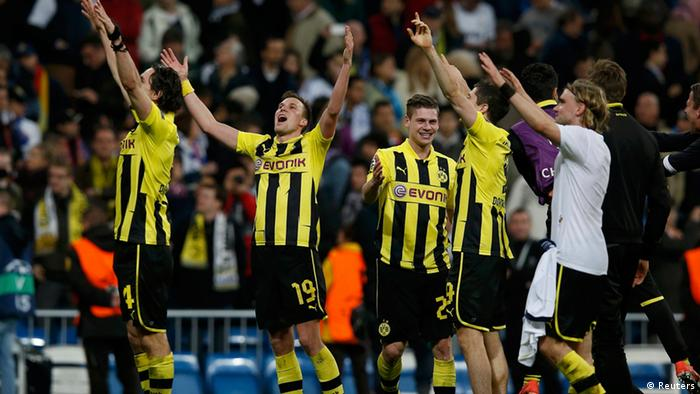 Borussia Dortmund players celebrate after the Champions League semi-final second leg soccer match against Real Madrid at Santiago Bernabeu stadium in Madrid April 30, 2013. Despite losing the match 2-0 Dotmund went through 4-3 on aggregate to play in the Champions League final on Tuesday . REUTERS/Juan Medina (SPAIN - Tags: SPORT SOCCER)
