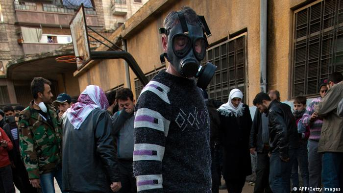 A man wearing a gas mask looks for his relatives amongst the bodies Syrian civilians executed and dumped in the Quweiq river lays in the grounds of the courtyard of a Yarmouk School, in the Bustan al-Qasr district of Aleppo, on January 29, 2013. The bodies of at least 65 young men, all executed with a single gunshot to the head or neck, were found in a river in Aleppo city, adding to the grim list of massacres committed during Syria's 22-month conflict. AFP PHOTO/JM LOPEZ (Photo credit should read JM LOPEZ/AFP/Getty Images)