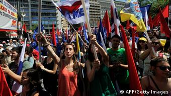 Communist-affiliated protesters hold flags in front of the Greek parliament during a May Day rally on May 1, 2013 in Athens. Greece's two main unions called a general strike against prolonged austerity on May Day, with protests planned . AFP PHOTO/ LOUISA GOULIAMAKI (Photo credit should read LOUISA GOULIAMAKI/AFP/Getty Images)