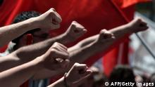 Demonstrators raise their fists during a demonstration on May 1, 2013. A strike stopped ferry services to the Greek islands and disrupted public transport in the capital Athens ahead of May Day protests Wednesday against Greece's prolonged economic austerity policies. AFP PHOTO / ARIS MESSINIS (Photo credit should read ARIS MESSINIS/AFP/Getty Images)