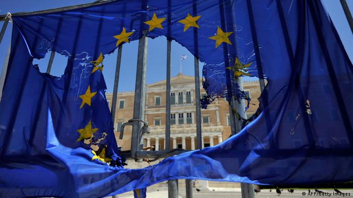 A burned EU flag hangs on the barriers protecting the Greek parliament in Athens on May 1, 2013. (Photo: LOUISA GOULIAMAKI/AFP/Getty Images)