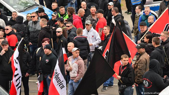 A large group of protestors - most of them men - wave red, white and black flags (Photo: Martin Schutt/dpa)