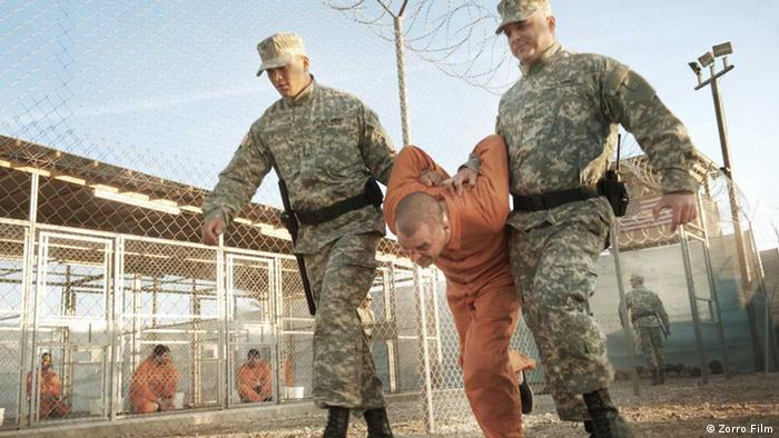A scene from the film Five Years, in which prison guards drag a prisoner across a compound