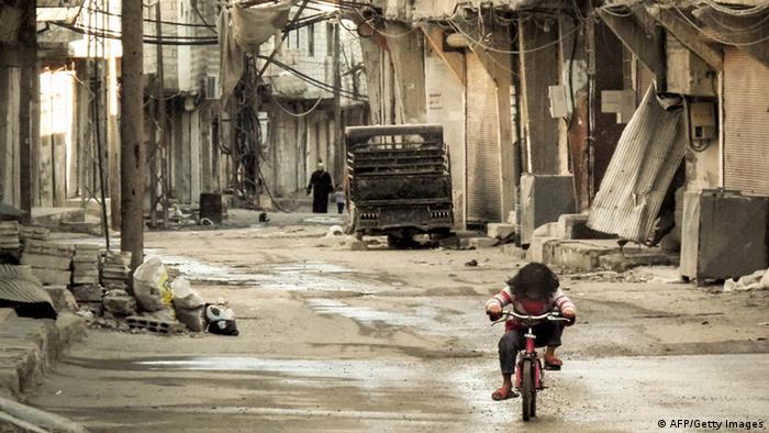 A Syrian girl rides her bicycle in an almost deserted street in the Teshrin neighborhood of the Qabun area in Damascus on January 3, 2013. US troops began arriving in Turkey to man Patriot missile batteries against threats from neighbouring Syria, where the 21-month conflict between the regime and rebels has escalated (photo: OMAR AL-KHANI/AFP/Getty Images).