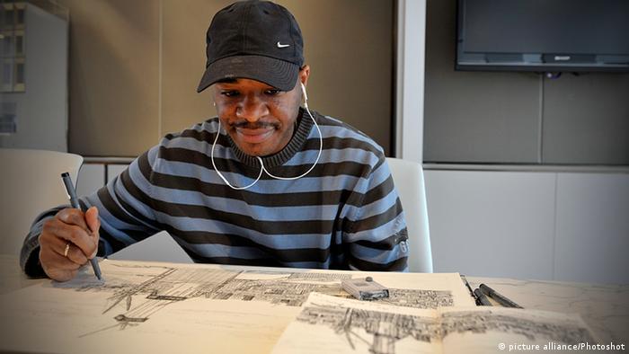 Stephen Wiltshire sitzt vor einer Zeichnung. (Copyright: picture alliance/Photoshot)