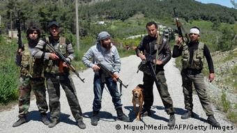 Rebel fighters from the Al-Ezz bin Abdul Salam Brigade pose for picture as they attend a training session at an undisclosed location near the al-Turkman mountains, in Syria's northern Latakia province, on April 24, 2013. AFP / MIGUEL MEDINA (Photo credit should read MIGUEL MEDINA/AFP/Getty Images)