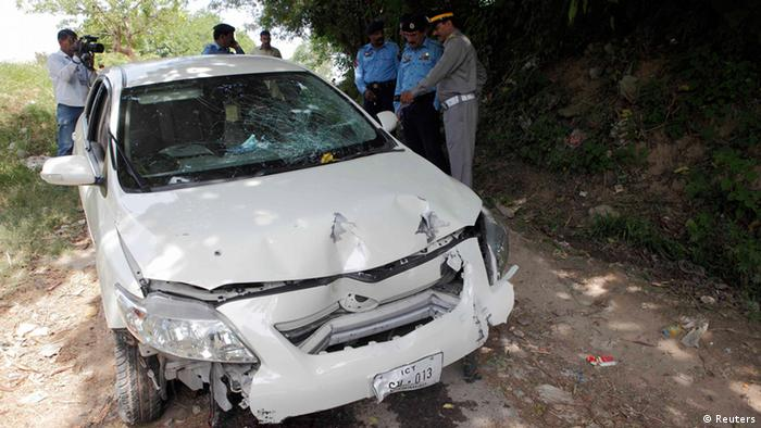Security officials inspect the damaged car, which prosecutor Chaudhry Zulfikar was travelling in, when he came under attack by unidentified gunmen, in Islamabad May 3, 2013. Zulfikar, the prosecutor investigating the 2007 assassination of former Pakistani Prime Minister Benazir Bhutto, one of the most shocking events in Pakistan's turbulent history, was shot dead on Friday, police sources said. Gunmen on a motorcycle pumped 12 bullets into Zulfikar as he left his home in Islamabad, the sources said. REUTERS/Mian Khursheed (PAKISTAN - Tags: POLITICS CIVIL UNREST CRIME LAW)