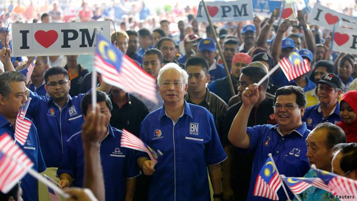 Malaysia's Prime Minister Najib Razak (C) waves a national flag as he sings patriotic songs with supporters during an election campaign rally in Rawang, outside Kuala Lumpur in this April 28, 2013 file picture. Boasting a fast-growing economy and riding a $2.6 billion deluge of government handouts to poorer voters, Najib would seem to have the recipe for electoral success on Sunday. Instead he faces what some say is a class war between aspiring young Malays and ethnic Chinese and Indian minorities against the rich, powerful and long-ruling Malay elite. REUTERS/Bazuki Muhammad/Files (MALAYSIA - Tags: POLITICS ELECTIONS BUSINESS)