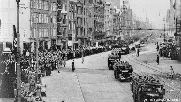 circa 1940: Nazi troops and armoured divisions driving along a main street in Amsterdam, (Photo by Three Lions/Getty Images)