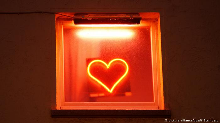 A red glowing neon heart on the front of a brothel in Frankfurt am Main.