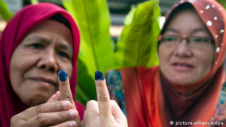 Malaysian woman show their inked fingers after they casting their votes in the country's May 2013 election. (Photo: Ahmad Yusni)