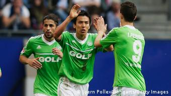 HAMBURG, GERMANY - MAY 05: Makoto Hasebe (C) of Wolfsburg celebrates after scoring his team's first goal during the Bundesliga match between Hamburger SV and VfL Wolfsburg at Imtech Arena on May 5, 2013 in Hamburg, Germany. (Photo by Joern Pollex/Bongarts/Getty Images)