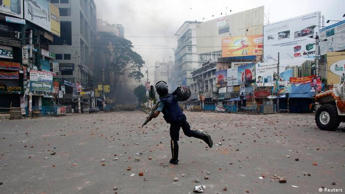 A police officer throws a piece of brick during a clash with activists of Hefajat-e-Islam in front of the national mosque in Dhaka May 5, 2013. At least one person was killed, more than one hundred injured, including journalists, and thirteen vehicles torched as activists from Hefajat-e Islam and Islami Chhatra Shibir clashed with police at the city's Paltan area. According to local media, Hefajat activists demanded for the introduction of blasphemy laws and a 13-point agenda, while blocking major roads in Dhaka. REUTERS/Andrew Biraj (BANGLADESH - Tags: POLITICS CIVIL UNREST RELIGION)
