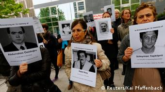 Protesters hold pictures of victims outside a courthouse, where the trial against Beate Zschaepe, a member of the neo-Nazi group National Socialist Underground (NSU), will start later today, in Munich May 6, 2013. The surviving member of NSU blamed for a series of racist murders that scandalised Germany and shamed its authorities goes on trial on Monday in one of the most anticipated court cases in recent German history. The trial in Munich will focus on 38-year-old Zschaepe, who is charged with complicity in the murder of eight Turks, a Greek and a policewoman between 2000-2007, as well as two bombings in immigrant areas of Cologne, and 15 bank robberies. REUTERS/Kai Pfaffenbach (GERMANY - Tags: CRIME LAW POLITICS CIVIL UNREST)