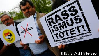 Protesters hold placards against racism in front of a courthouse, where the trial against Beate Zschaepe, a member of the neo-Nazi group National Socialist Underground (NSU), will start later today, in Munich May 6, 2013. The surviving member of the NSU blamed for a series of racist murders that scandalised Germany and shamed its authorities goes on trial on Monday in one of the most anticipated court cases in recent German history. The trial in Munich will focus on 38-year-old Zschaepe, who is charged with complicity in the murder of eight Turks, a Greek and a policewoman between 2000-2007, as well as two bombings in immigrant areas of Cologne, and 15 bank robberies. REUTERS/Kai Pfaffenbach (GERMANY - Tags: CIVIL UNREST CRIME LAW POLITICS)