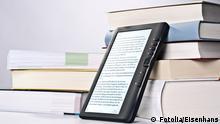 Ein eReader an einen Bücherstapel gelehnt