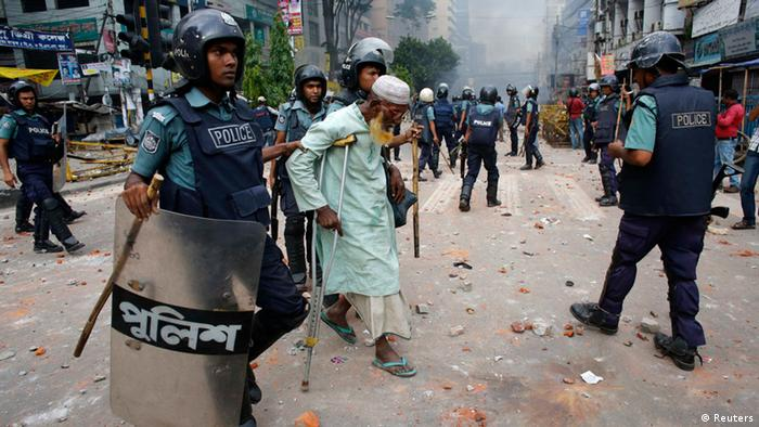 Police officers help a man cross a street during a clash with activists of Hefajat-e Islam in front of the national mosque in Dhaka May 5, 2013. At least one person was killed, more than one hundred injured, including journalists, and thirteen vehicles torched as activists from Hefajat-e Islam and Islami Chhatra Shibir clashed with police at the city's Paltan area. According to local media, Hefajat activists demanded for the introduction of blasphemy laws and a 13-point agenda, while blocking major roads in Dhaka. REUTERS/Andrew Biraj (BANGLADESH - Tags: POLITICS CIVIL UNREST RELIGION)