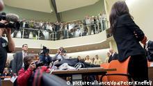 Die Angeklagte Beate Zschäpe (r) steht zum Prozessauftakt am 06.05.2013 im Gerichtssaal in München (Bayern). Vor dem Oberlandesgericht beginnt heute der Prozess um die Morde und Terroranschläge des «Nationalsozialistischen Untergrunds» (NSU). Das Verfahren gilt schon heute als einer der bedeutendsten Strafprozesse in der Geschichte der Bundesrepublik. Foto: Peter Kneffel/dpa