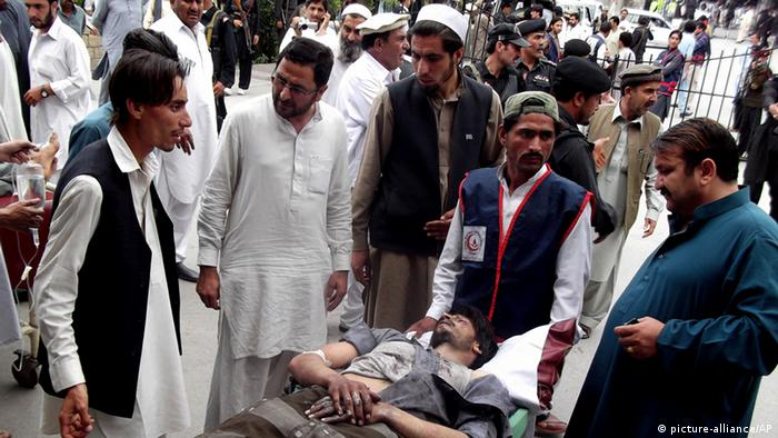 People stand near a man injured from an explosion, at a local hospital in Pakistani tribal area of Parachinar, Monday, May 6, 2013 (Photo: AP Photo/Ali Murtaza)