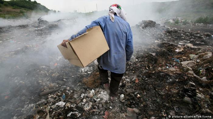 A person carries a cardboard box as they walk through a rubbish dump