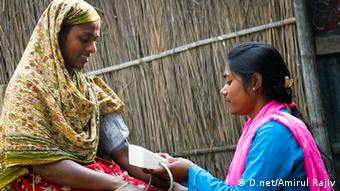 An Infolady takes a villager's blood pressure (Photo:D.net/Amirul Rajiv)