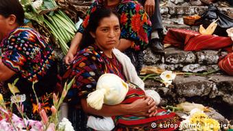 A woman holds a child in a market