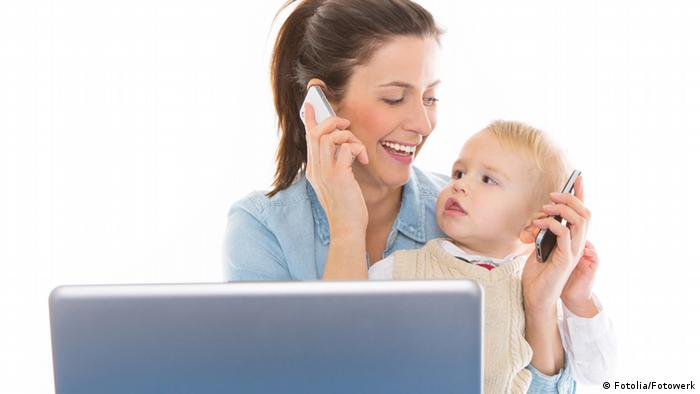 A woman seated in front of a claptop holds up a baby as she telephones