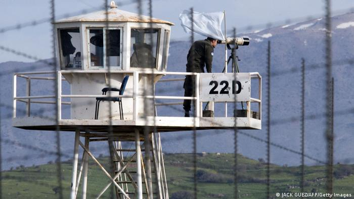 A UN peacekeeper uses his binoculars on an observation tower in the demilitarized United Nations Disengagement Observer Force (UNDOF) zone, in the Golan Heights. (Photo: Jack Guez / AFP / Getty Images)