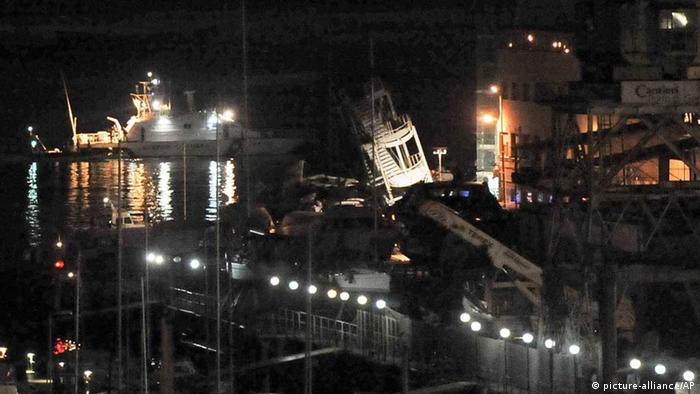 The toppled control tower, center, of the port of Genoa, northern Italy, is lit by rescuers after a cargo ship slammed into it killing at least three people, Tuesday, May 7, 2013. A half-dozen people remain unaccounted for early Wednesday, after a cargo ship identified as the Jolly Nero of the Ignazio Messina & C. SpA Italian shipping line, slammed into the port. An Italian Coast Guard vessel (Photo: AP Photo/Francesco Pecoraro)