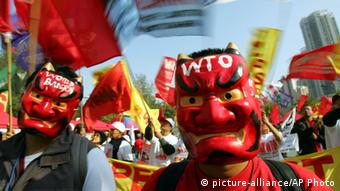 Masked protesters lead the flag-waving march from Hong Kong's Victoria Park towards the Hong Kong Convention and Exhibition Center Saturday, Dec. 17, 2005 in continuing protest against the 6th WTO Ministerial Conference in this former British colony. The activists have been holding daily protests against the global trade body while trade delegates were huddling in a last-ditch effort to hammer out a watered-down compromise deal to save the WTO summit from flopping completely. (AP Photo/Bullit Marquez)