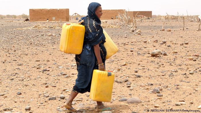 A woman in Mauritania carries cans to fill them with water (Photo: ABDELHAK SENNA/AFP/GettyImages)