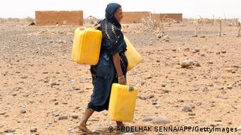 A woman carries cans to fill them with water in Katawane, near Nema, southeastern Mauritania, on May 4, 2012 (Photo: Abdelhak Senna)