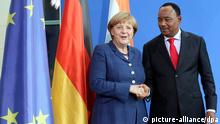Merkel shakes Issoufou's hand in front of German and EU flags