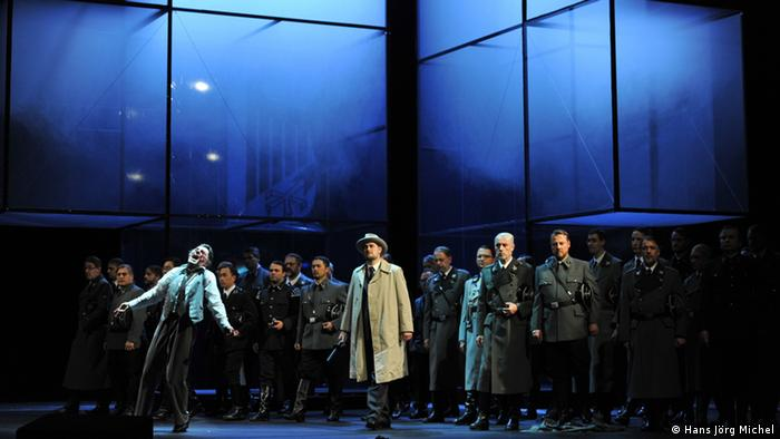 A scene from the premiere of the Tannenhäuser opera directed by Burkhard Kosminski in Düsseldorf. Much of the cast is visible in front of some large glass areas, filled with smoke/fog. (Photo: Hans Jörg Michel, Düsseldorf, 2013