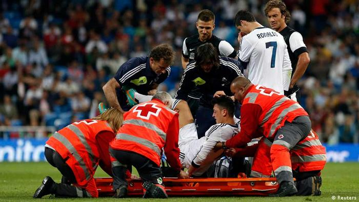 Real Madrid's Mesut Ozil (C) is helped onto a stretcher during their Spanish first division soccer match against Malaga at Santiago Bernabeu stadium in Madrid May 8, 2013. REUTERS/Susana Vera (SPAIN - Tags: SPORT SOCCER)