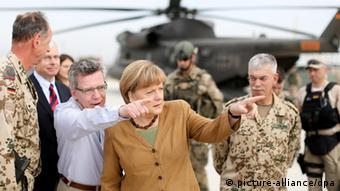 In a desert setting with a helicopter in the background, Thomas de Maiziere and Angela Merkel, flanked by German troops, point toward something off-camera. (Photo: Kay Nietfeld/dpa)