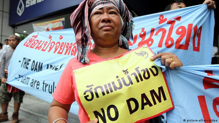 Thai villagers hold banners reading 'Love Mekong, No Dam' during a demonstration to protest against the proposed dam 'Xayaburi', in front of Ch Karnchang headquarters, a construction company in Bangkok, Thailand, 19 April 2011