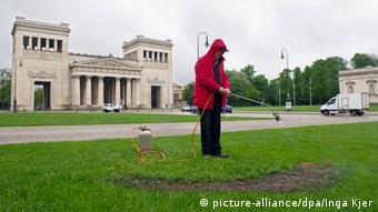 Aktionskünstler Kastner brennt auf dem Münchner Königsplatz ein Loch in den Rasen (Foto: picture-alliance/dpa/Inga Kjer)