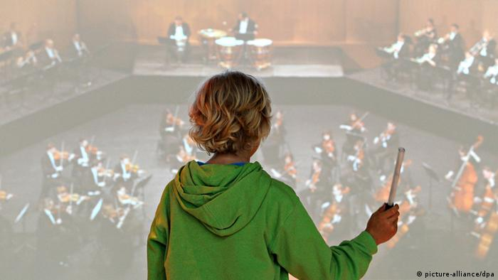 Child stands before a video screen and conducts an imaginary orchestra (picture-alliance/dpa)