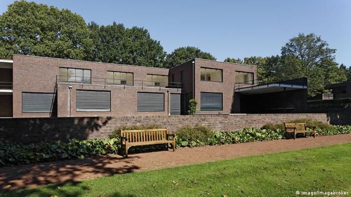 Double-story rectangular dark-brown brick structure in a park setting (imago/imagebroker)