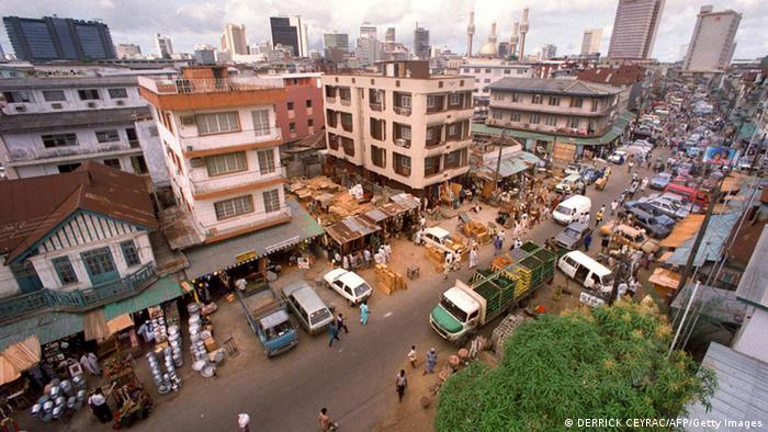 Aerial view of a street in Lagos with skyscrapers visible in the background.