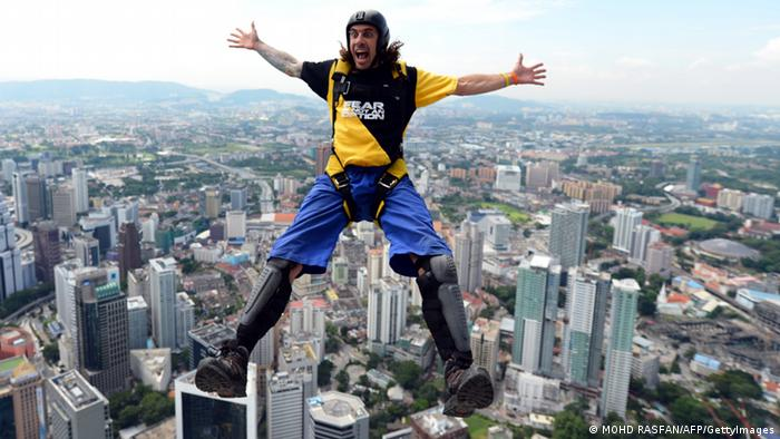 Base jumper Chris McDougall from Australia leaps from the top of the 421-metre Kuala Lumpur Tower during the International Tower Jump in Kuala Lumpur on September 27, 2012. Some 95 professional basejumpers from 18 countries are taking part in the annual event. AFP PHOTO / MOHD RASFAN (Photo credit should read MOHD RASFAN/AFP/GettyImages)