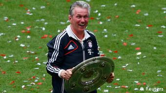 Bayern Munich's coach Jupp Heynckes holds the trophy as his team celebrates after their German first division Bundesliga soccer match against Augsburg in Munich, May 11, 2013. Bayern held their 23rd German league title on Saturday after a comfortable 3-0 over Augsburg as they prepare for the all-German Champions League final against Borussia Dortmund in two weeks. REUTERS/Michael Dalder (GERMANY - Tags: SPORT SOCCER TPX IMAGES OF THE DAY) DFL RULES TO LIMIT THE ONLINE USAGE DURING MATCH TIME TO 15 PICTURES PER GAME. IMAGE SEQUENCES TO SIMULATE VIDEO IS NOT ALLOWED AT ANY TIME. FOR FURTHER QUERIES PLEASE CONTACT DFL DIRECTLY AT + 49 69 650050.