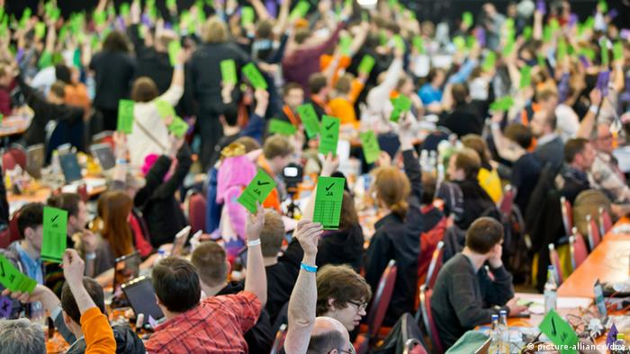 Delegates hold up green voting flyers at the German Pirate Party convention
