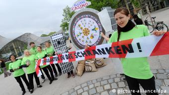 A group of protesters with a cardboard Wheel of Fortune that on the streets in Munich. (Photo: Tobias Hase/dpa)