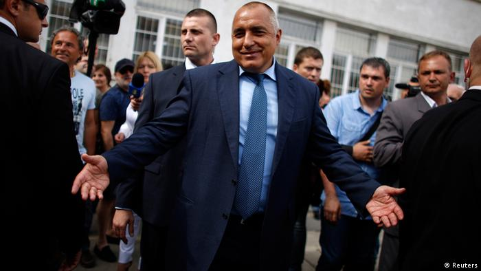 Leader of centre-right GERB party Boiko Borisov gestures as he leaves a polling station after casting his vote in Sofia May 12, 2013. Bulgarians voted on Sunday in an election marred by suspicions of rigging, with expectations of a close result that is likely to prolong uncertainty in the European Union's poorest country. REUTERS/Stoyan Nenov (BULGARIA - Tags: POLITICS ELECTIONS)