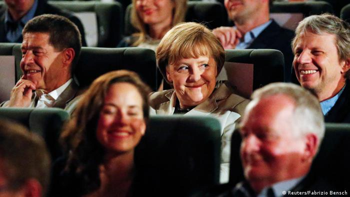 German Chancellor Angela Merkel (C), her husband Joachim Sauer (L) and German film director Andreas Dresen (R) wait for the screening of the former East German classic film The Legend of Paul and Paula at a cinema in Berlin, May 12, 2013. Merkel was invited to select the movie for Sunday evening's film screening, as part of the German Film Academy series My Film, where a prominent figure from the political or cultural sphere chooses a film for the evening and explains its significance to audiences. REUTERS/Fabrizio Bensch (GERMANY - Tags: ENTERTAINMENT POLITICS TPX IMAGES OF THE DAY)