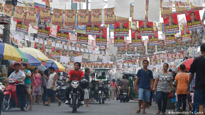 Election posters for the midterm elections hang along a street as residents walk to a polling precinct in Taguig, Metro Manila May 13, 2013. More than 50 million Filipinos will cast their votes for a new set of lawmakers and local officials on Monday, a referendum of sorts halfway through the six-year term of Philippine President Benigno Aquino who tackled corruption and restored business confidence that led to credit-rating upgrades. REUTERS/Erik De Castro (PHILIPPINES - Tags: POLITICS ELECTIONS)