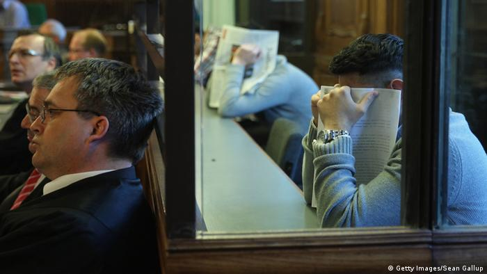 BERLIN, GERMANY - MAY 13: Co-defendants hide their faces as he they sit behind a glass partition in the courtroom on the first day of the trial of the six Jonny K. attackers at the Kriminalgericht Moabit court on May 13, 2013 in Berlin, Germany. The six young men are accused of assaulting Jonny K. in front of a bar on Alexanderplatz on October 14, 2012, and beating him so severely that Jonny K. later died of his head injuries. His sister Tina has led a media campaign to draw publicity to the case and the issue of violence in German society. (Photo by Sean Gallup/Getty Images)